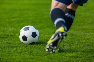 A young man kicks a soccer ball across the field as part of Retorno's sports therapy program.